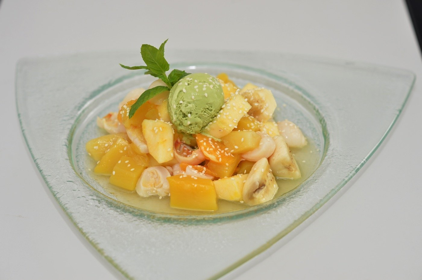 Asian fruit salad with green tea ice cream and ground sesame seeds