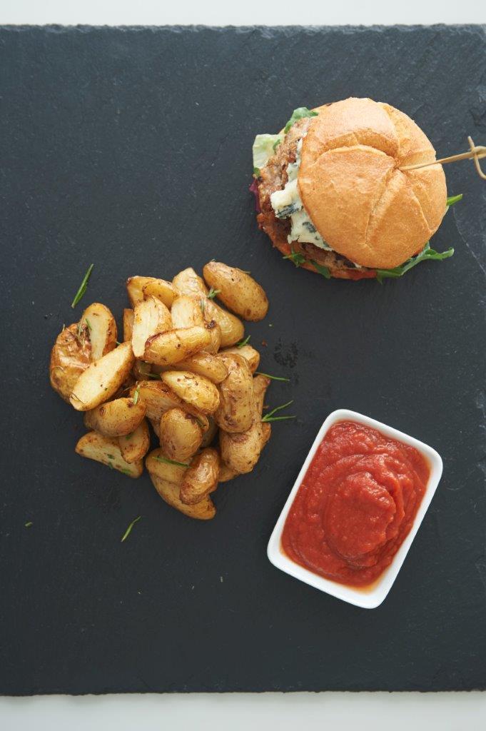 Μπέρκερς κοτόπουλο με καραμελωμένο κρεμμύδι και μπλέ τυρί. Συνοδεύονται με σπιτική κέτσαπ και πατάτες φούρνου με δεντρολίβανο